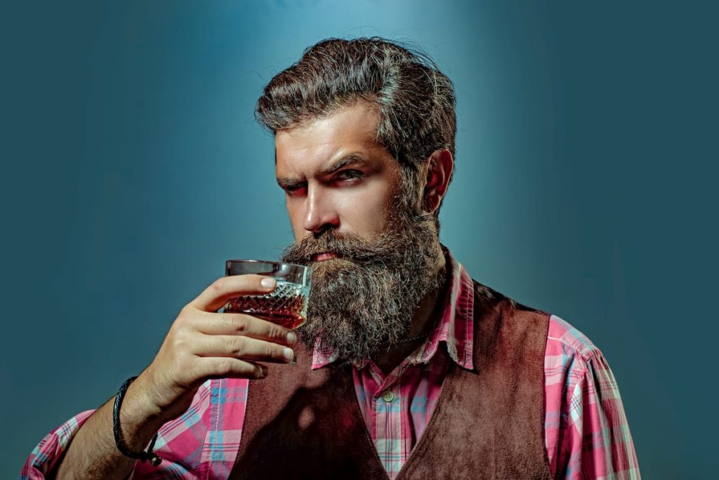 Bearded handsome man holding glass of whiskey. Alcohol concept. Alcohol Drink. Retro vintage man with whiskey or scotch - Can You Drink Alcohol on a Carnivore Diet