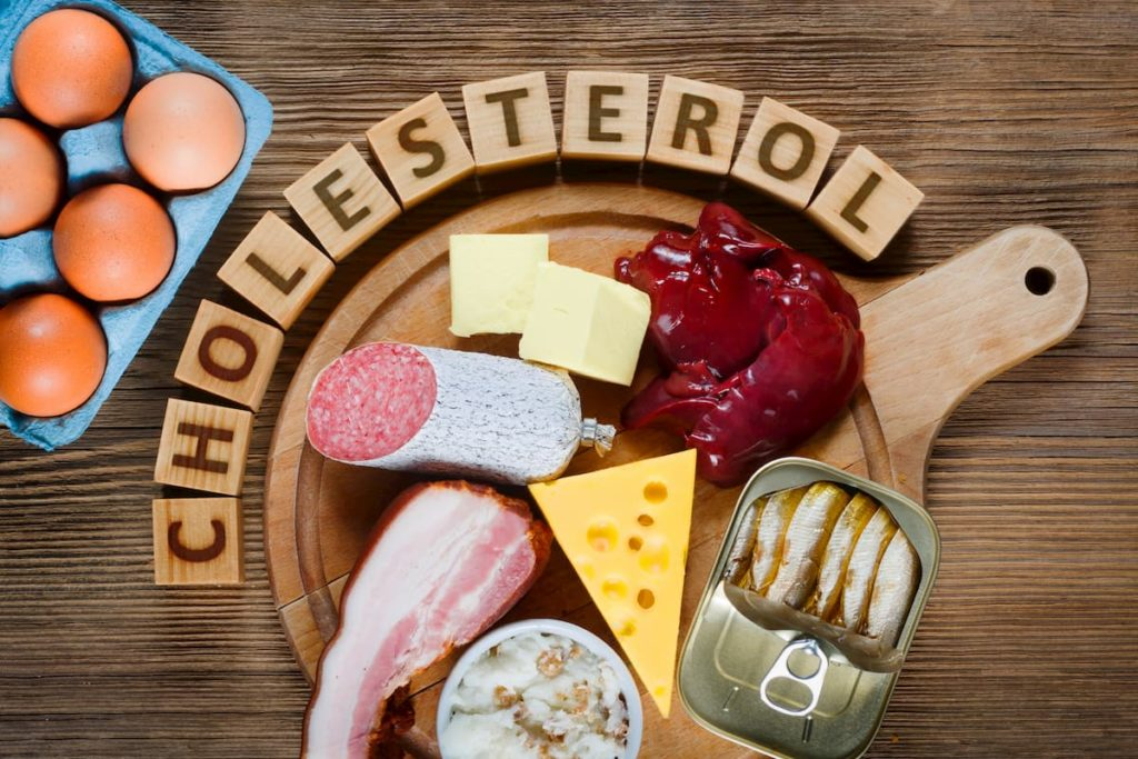 Cholesterol spelled out with blocks, meat on a table - How Does the Carnivore Diet Affect Cholesterol