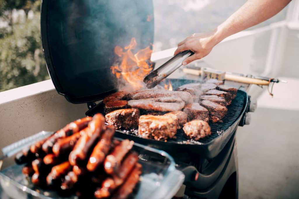 Close-up of man grilling lots of meat on barbecue with flames - Carnivore Diet Eating Plan